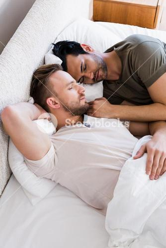 Happy gay couple sleeping together on bed