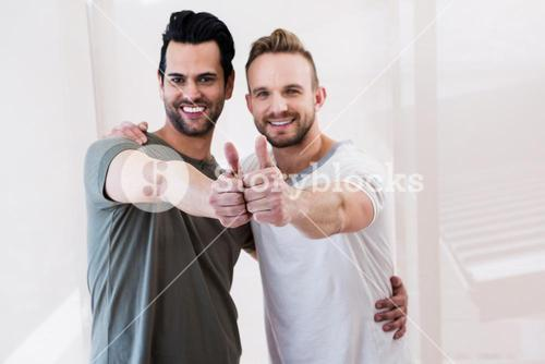 Smiling gay couple showing thumbs up