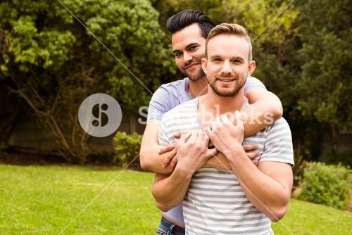 Smiling gay couple hugging