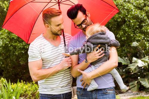 Smiling gay couple with child