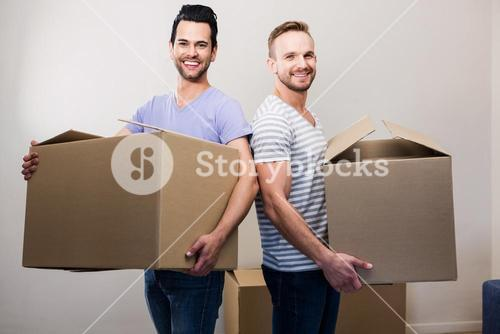Happy gay couple holding boxes