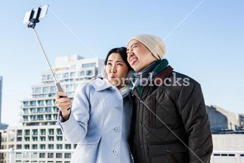 Playful couple taking selfie against building