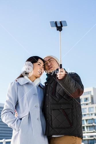 Couple making face and clicking pictures using selfie stick
