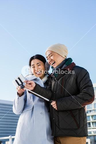 Couple laughing at their pictures taken on smartphone