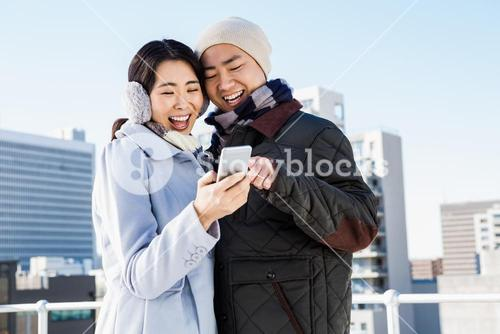 Cheerful couple looking at the smart phone