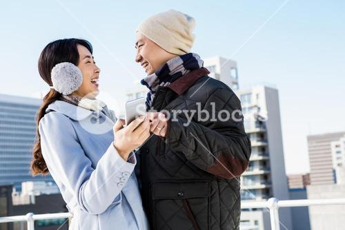 Couple laughing while holding smartphone