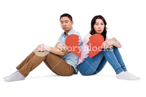 Portrait of sad couple holding broken heart pieces