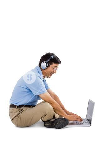 Side view of cheerful man listening music while using laptop