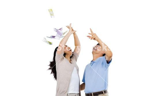 Happy couple throwing money in the air