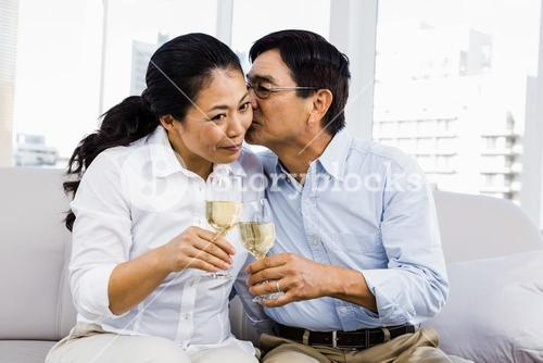 Man kissing woman with glasses of wine