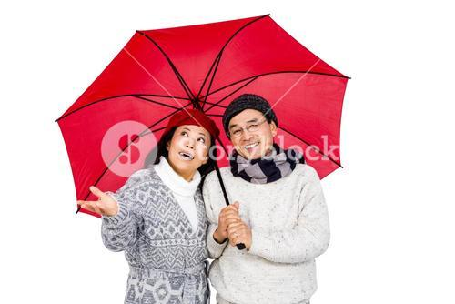 Older asian couple under umbrella