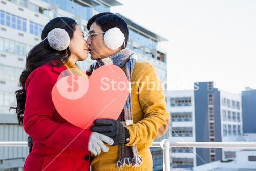 Older asian couple showing a heart