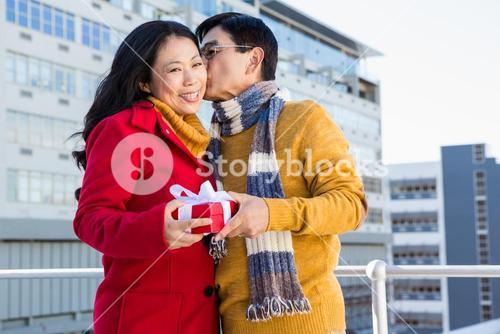 Older asian couple on balcony with gift