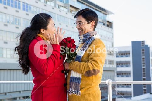 Older asian couple on balcony with roses