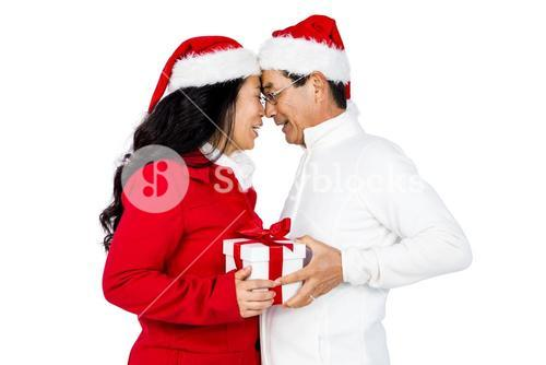 Festive senior couple exchanging gifts