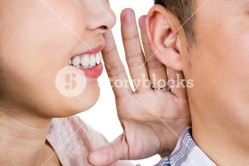 Cropped image of woman whispering secret to husband
