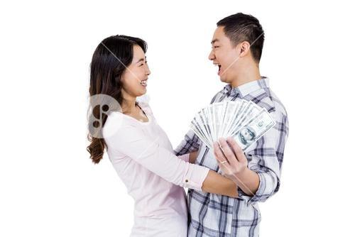 Cheerful happy couple holding money while standing