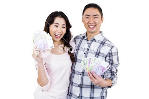 Portrait of happy cheerful couple holding money