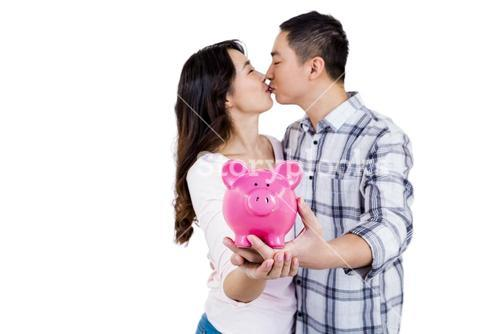 Couple kissing while holding piggy bank