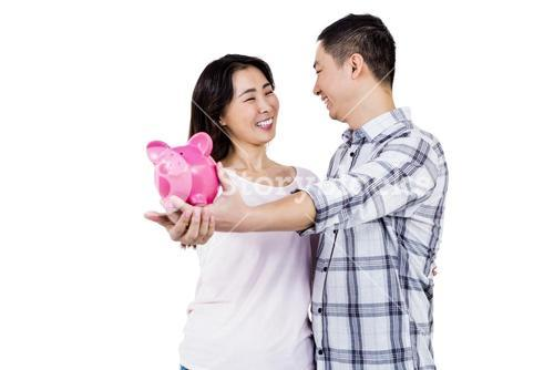 Happy couple looking at each other while holding piggy bank