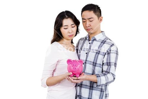 Couple holding their piggy bank