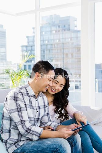 Young happy couple looking at digital tablet