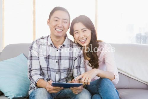 Young happy couple holding digital tablet