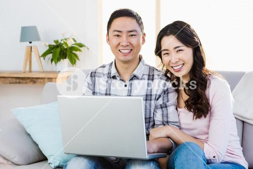 Smiling young couple using laptop
