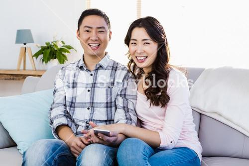 Smiling couple relaxing on sofa