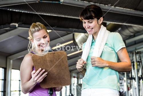 Two smiling women looking at notes