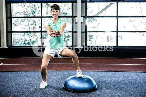 Fit woman doing exercise with bosu ball