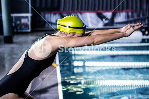 Swimmer woman about to dive into swimming pool