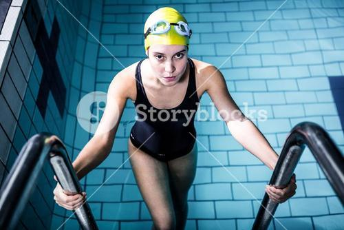 Smiling swimmer woman getting out of the swimming pool