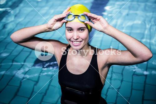 Smiling swimmer woman holding her swimming glasses