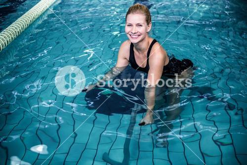 Smiling woman cycling in the swimming pool