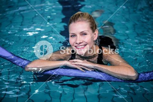 Fit smiling woman with a foam roller