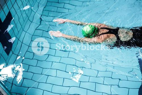 Fit woman swimming with swimming hat
