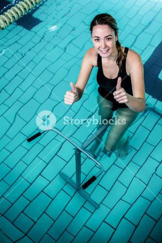 Fit woman cycling with thumbs up
