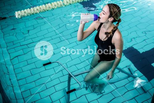 Fit woman cycling while drinking water