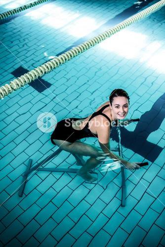 Fit smiling woman cycling on a swimming bike
