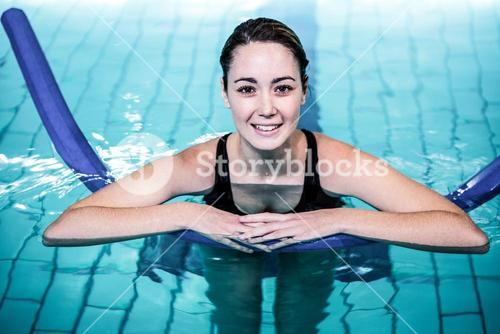 Fit smiling woman swimming with a foam roller