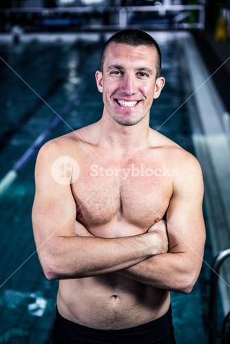 Smiling muscular swimmer with arms crossed