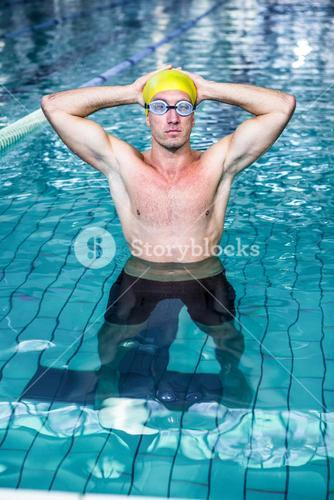 Fit swimmer holding his head with his hands