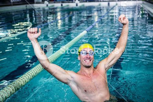 Happy swimmer put his hands up