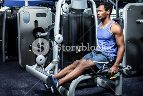 Serious muscular man using exercise machine