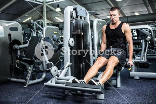 Muscular man using exercise machine for legs