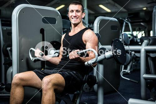 Smiling muscular man using exercise machine