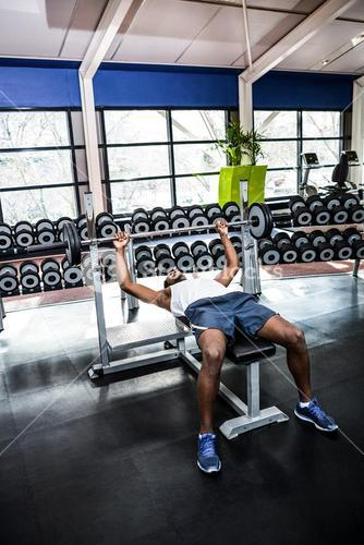 Muscular man lifting barebell while lying on bench