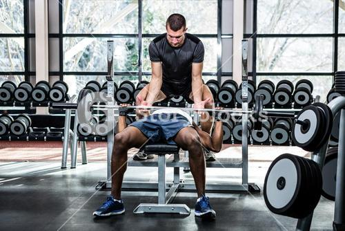 Trainer helping muscular man lifting barebell
