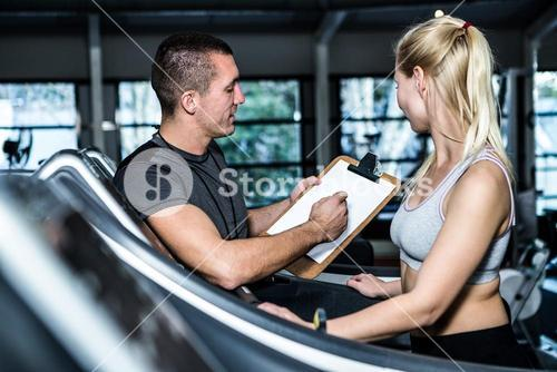 Fit woman with trainer using treadmill